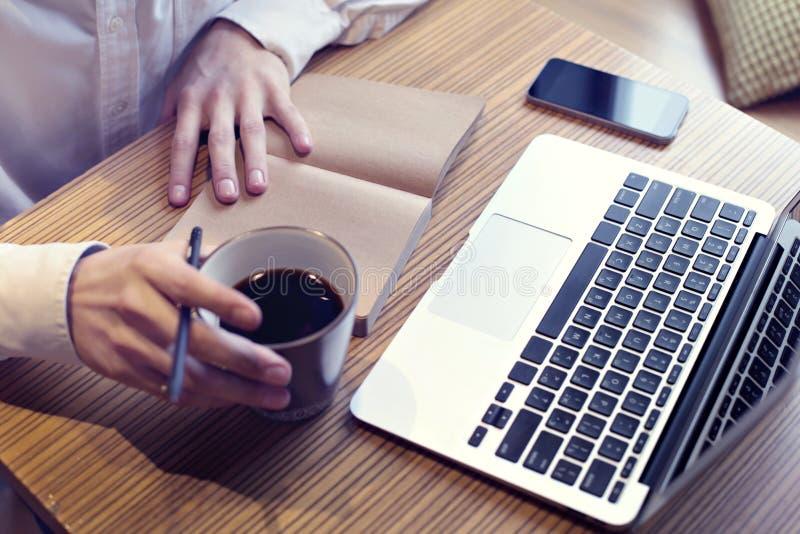 商人饮用的咖啡和研究便携式计算机,手机,写经营计划,佩带的白色衬衣 免版税库存照片