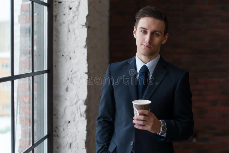 商人饮用的咖啡在站立近的窗口的办公室看照相机 库存图片