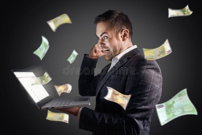 商人高兴在从膝上型计算机的金钱飞行 概念网上收入,赌博,自由职业者 免版税图库摄影