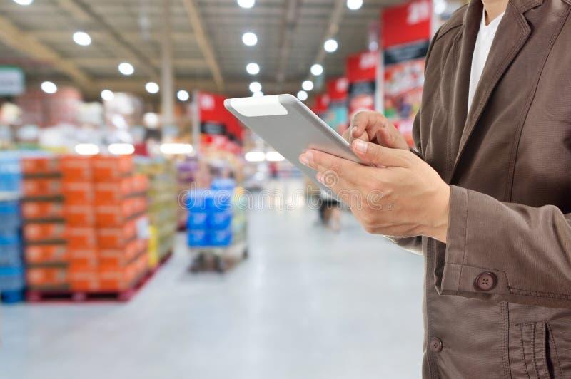 商人,饲槽用途流动片剂的手在超级市场 库存图片