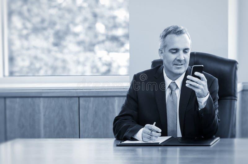 商人读书在他的电话的正文消息 库存图片