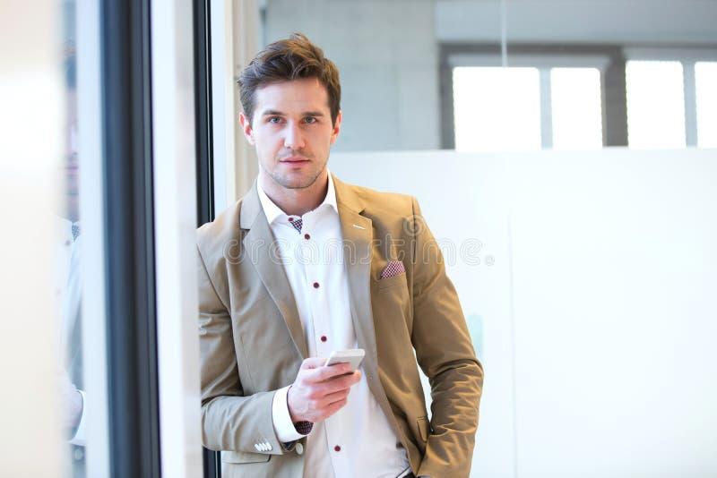 年轻商人画象与倾斜在窗口的手机的在办公室 免版税库存图片