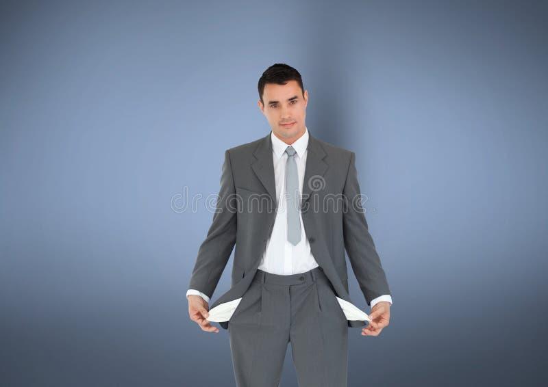 商人画象与站立反对灰色背景的空的口袋的代表金钱 库存照片