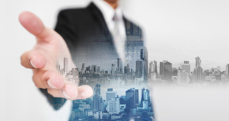 商人延长手,有两次曝光城市和房地产站点建筑的和全息图未来派城市 免版税库存照片