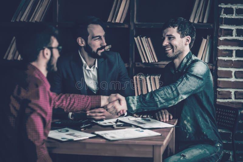 商务伙伴在谈论合同以后握手在t 免版税库存图片
