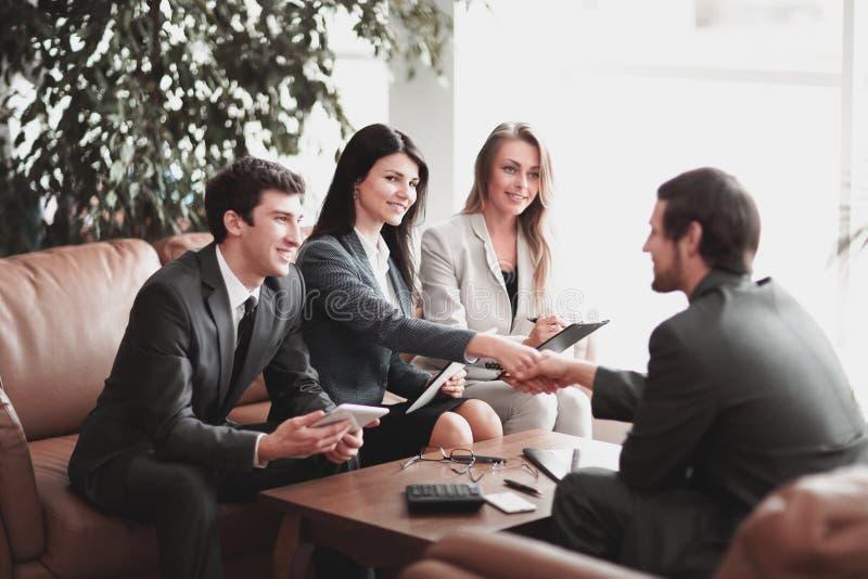 商务伙伴握手在一张书桌的在一个现代办公室 库存照片