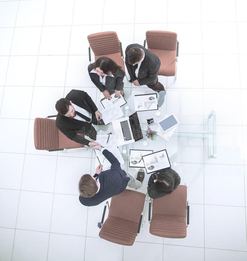 商务伙伴握手在谈话前的在桌面附近 免版税图库摄影