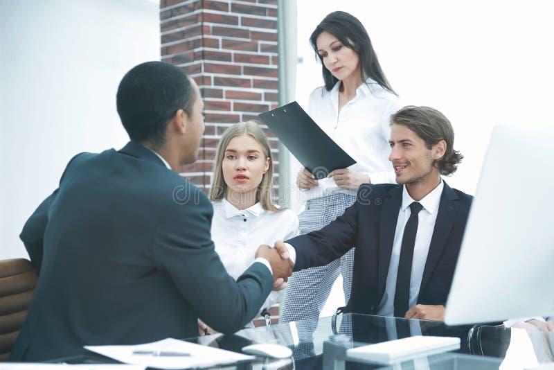 商务伙伴握手在meetinig的在现代办公楼 库存图片