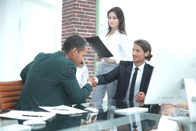 商务伙伴握手在meetinig的在现代办公楼 图库摄影