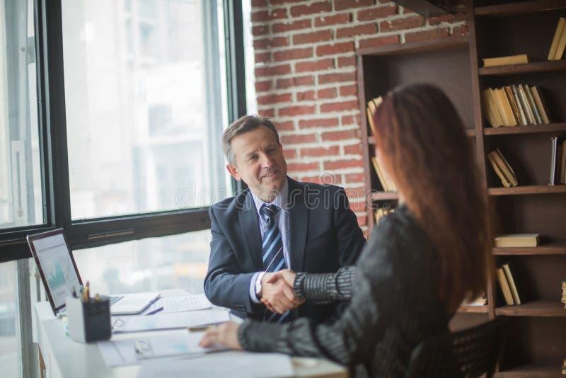 商务伙伴握手坐在他们的书桌的 图库摄影