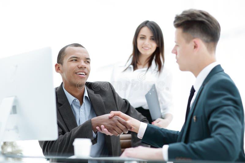 商务伙伴握手坐在桌书桌的 库存图片