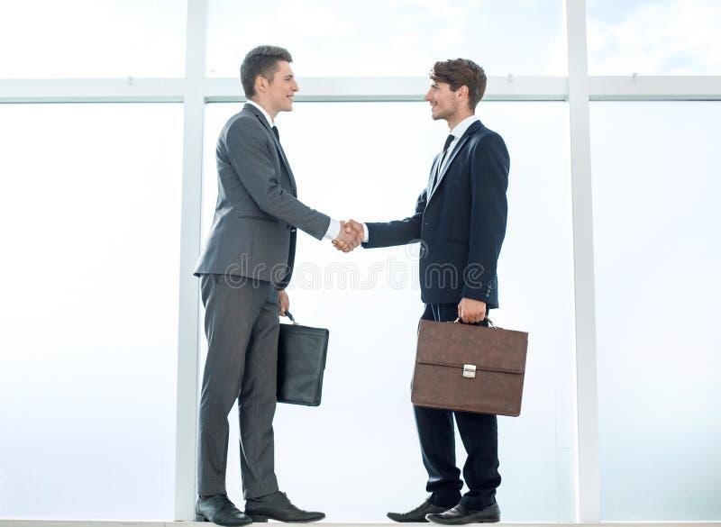 商务伙伴握手站立在大办公室风附近的 库存图片