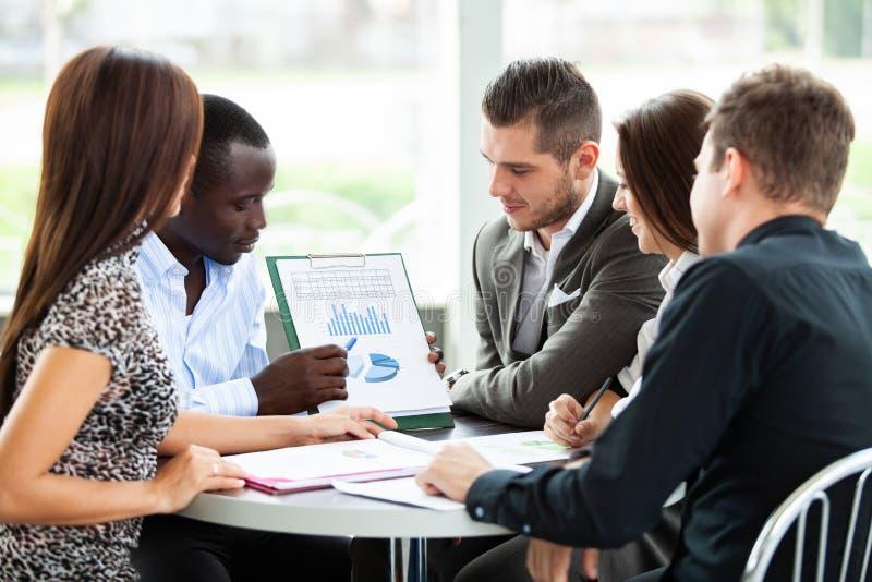 商务伙伴的图象谈论文件和想法在会议上 免版税库存图片