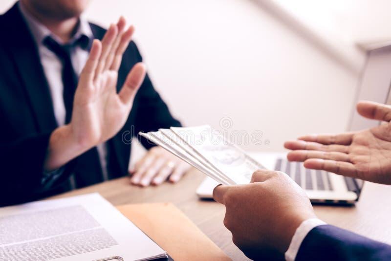商务伙伴递交欺骗现金给男性商人在办公室拒绝收受贿赂的企业家 免版税库存照片