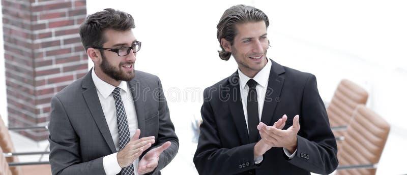 商务伙伴鼓掌,站立在办公室 免版税图库摄影