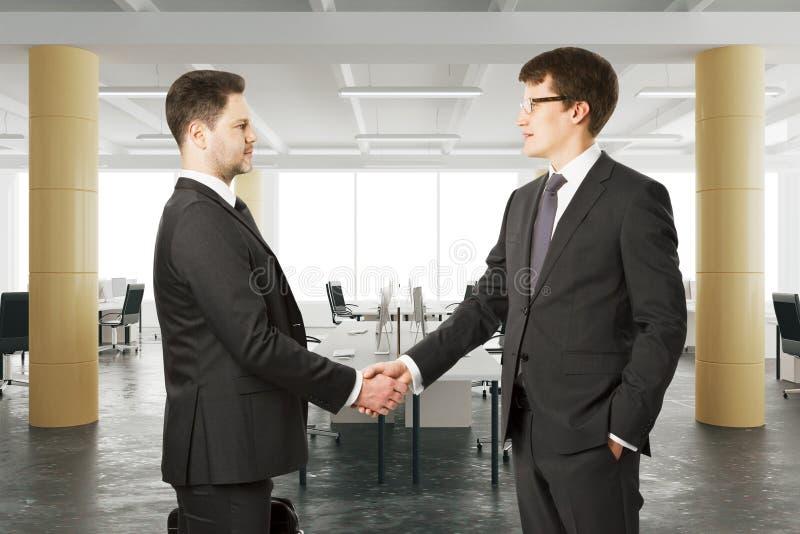 商务伙伴在现代露天场所办公室握他们的手 免版税图库摄影