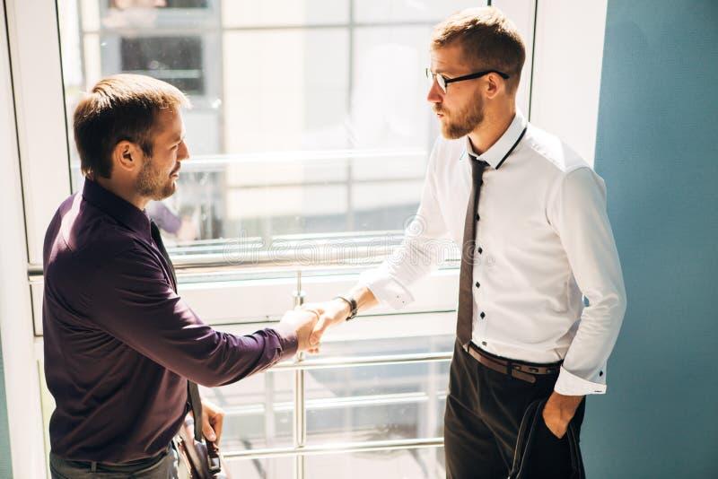 商务伙伴握手在办公楼的台阶见面了 免版税库存图片