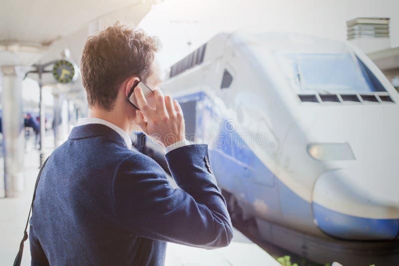 商务旅游,商人谈话由电话在火车站,当等待火车时 免版税库存照片