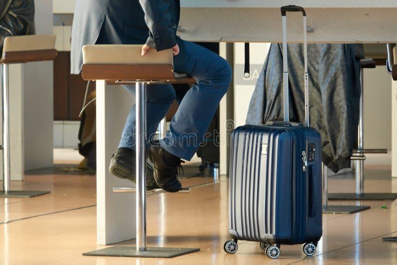 商务旅游 带着一个现代手提箱的一个人坐一个高凳在机场 免版税库存照片