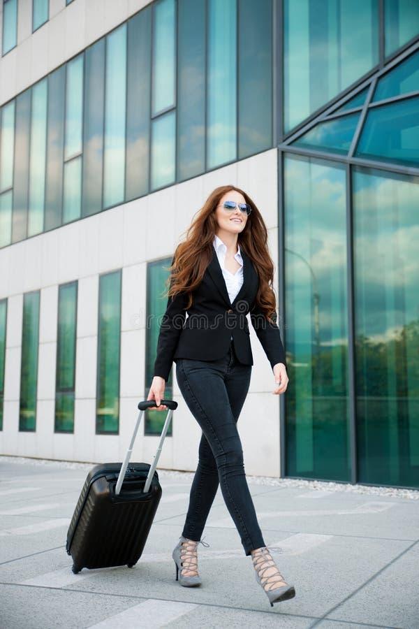 商务旅游-带着手提箱的妇女在机场buil之外走 库存图片