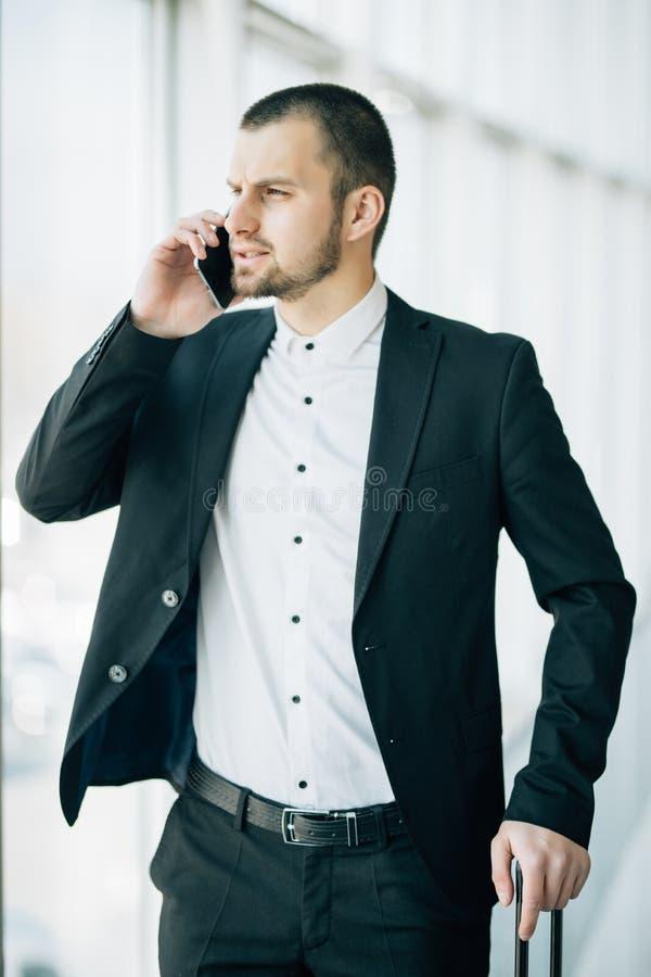 商务旅行的英俊的年轻人走与他的行李和谈话在手机在机场 做酸碱度的旅行的商人 库存照片