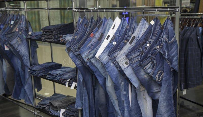 商店仓库、男人和妇女,男女皆宜的牛仔裤牛仔布裤子,很多牛仔裤裤子,销售 免版税库存图片