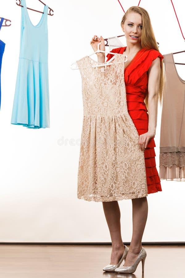 商店或衣橱采摘礼服的妇女 免版税库存图片