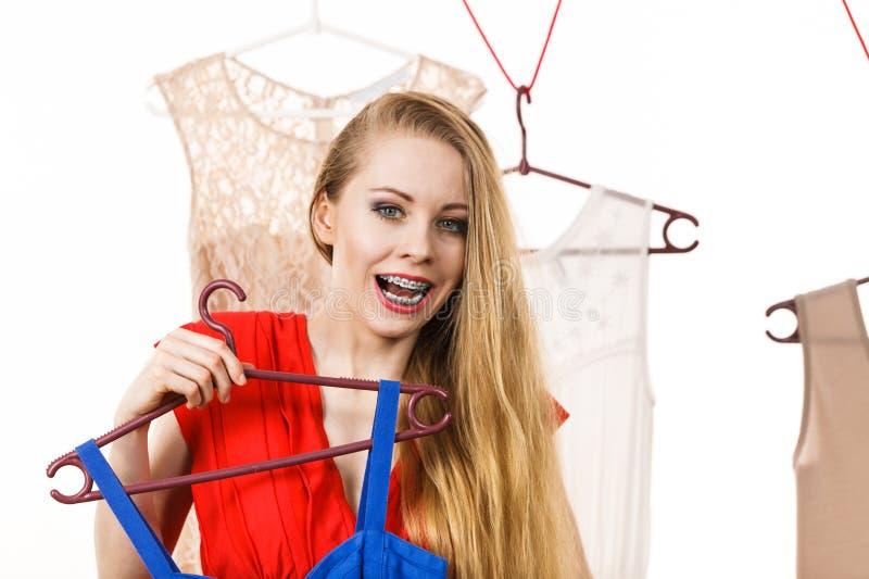 商店或衣橱采摘礼服的妇女 图库摄影