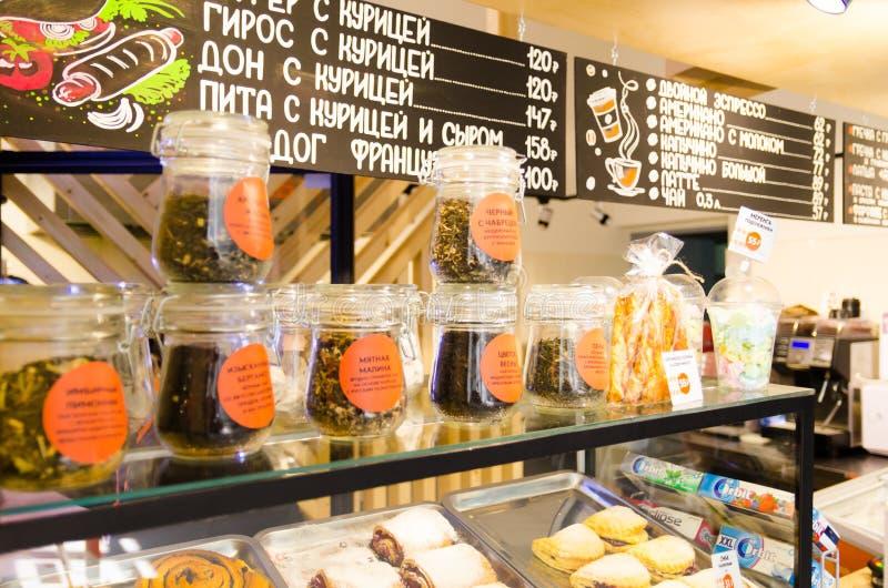 商店窗口咖啡馆用酥皮点心和叶子茶与价牌用俄语 免版税库存照片