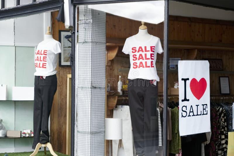 商店窗口销售标志妇女给红色白色横幅购物的零售购物中心穿衣 免版税图库摄影