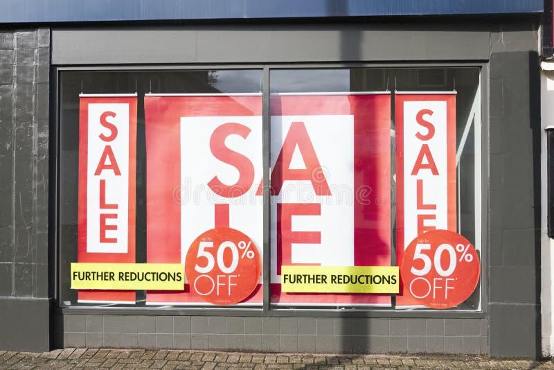 商店窗口销售标志给红色白色横幅商店穿衣 免版税库存图片