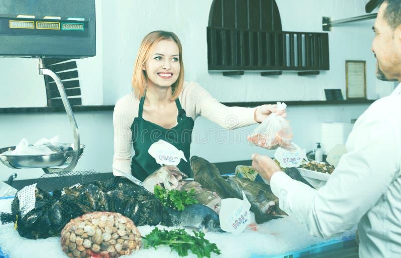 商店雇员愉快的美丽的销售的鲜鱼和变冷的海 库存图片