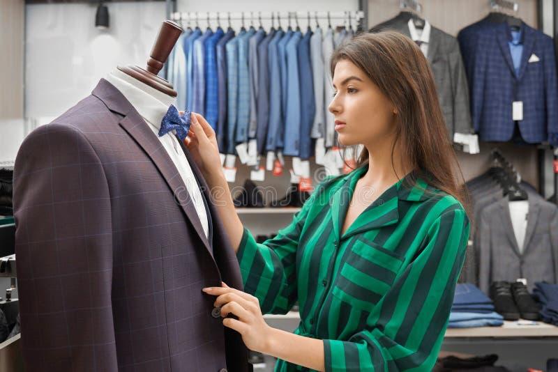 商店顾问与衣物一起使用在商店 库存照片