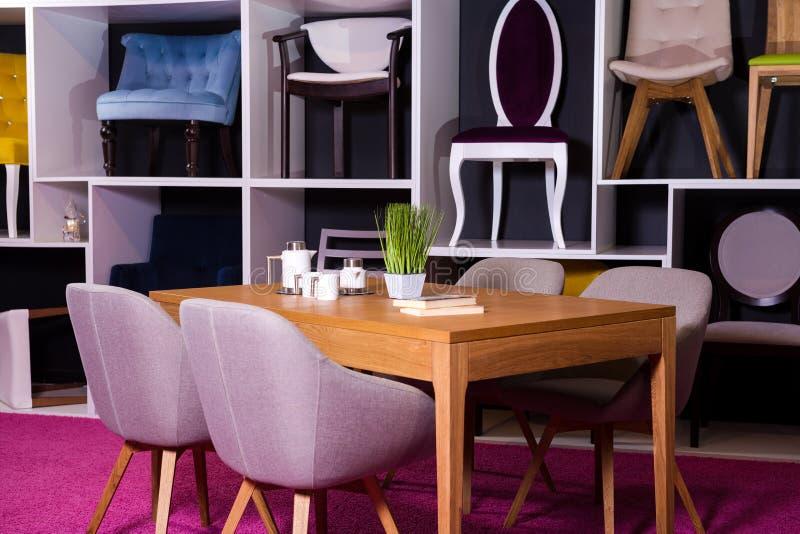 商店,家具销售在购物中心 用餐与纺织品椅子的博览会样品木桌在一个白色架子w的灰色 图库摄影