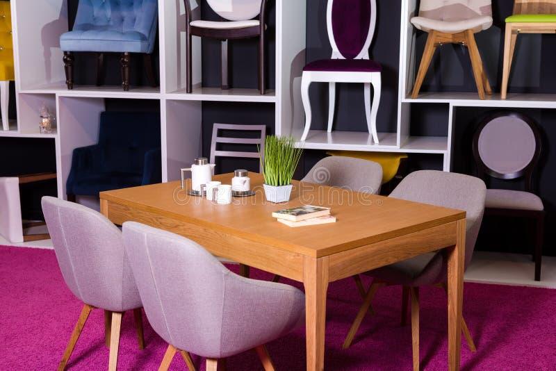 商店,家具销售在购物中心 用餐与纺织品椅子的博览会样品木桌在一个白色架子w的灰色 免版税库存照片