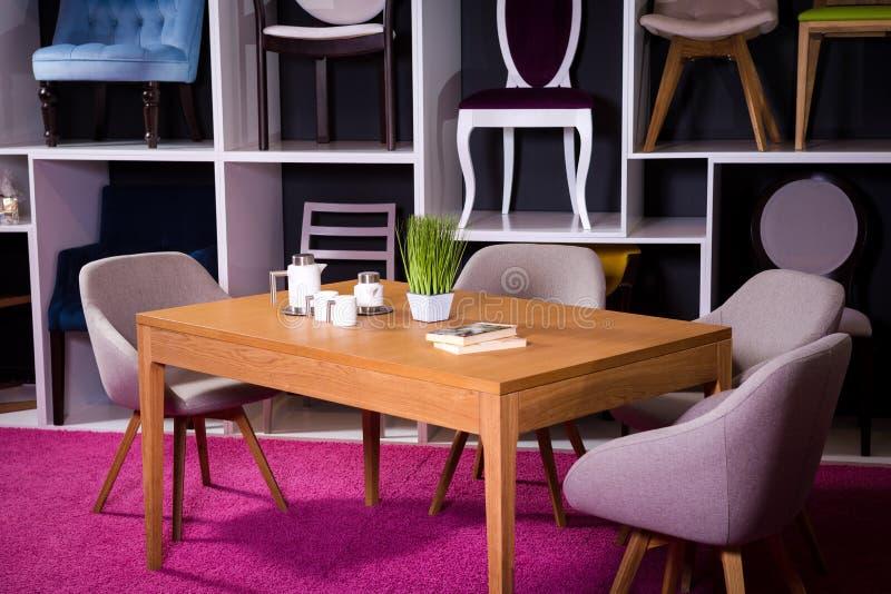 商店,家具销售在购物中心 用餐与纺织品椅子的博览会样品木桌在一个白色架子w的灰色 免版税图库摄影