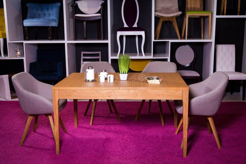 商店,家具销售在购物中心 用餐与纺织品椅子的博览会样品木桌在一个白色架子w的灰色 库存照片