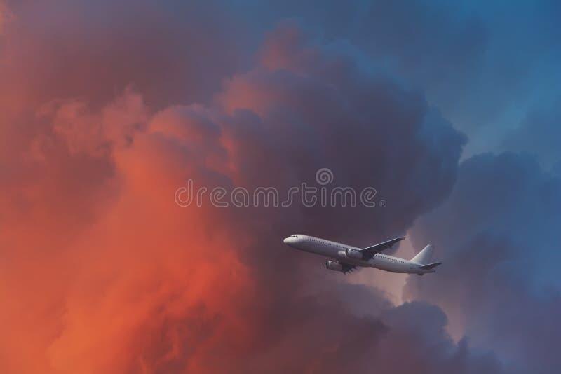 商用飞机在夕阳光下飞过云层 旅行概念 软焦点 色调 免版税库存照片