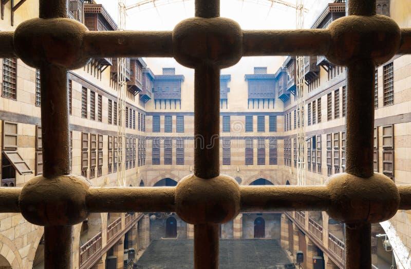 商队投宿的旅舍Wikala AlGhuri通过与铁华丽栅格的窗口,开罗,埃及庭院的看法  免版税库存图片
