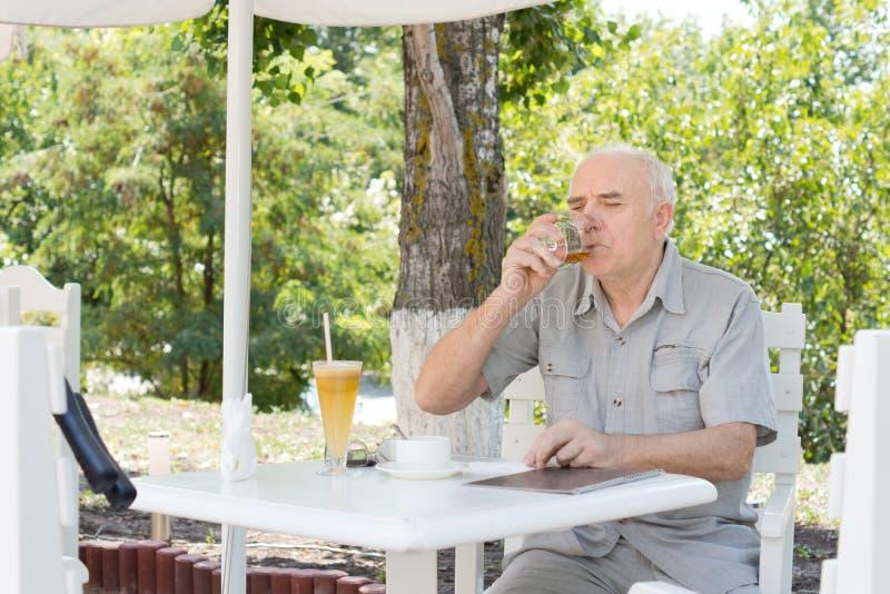 啜饮一杯白兰地酒的年长人 免版税库存照片