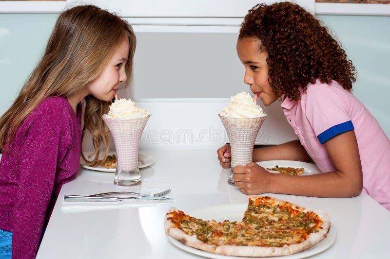 啜饮草莓奶汁的女孩 库存照片