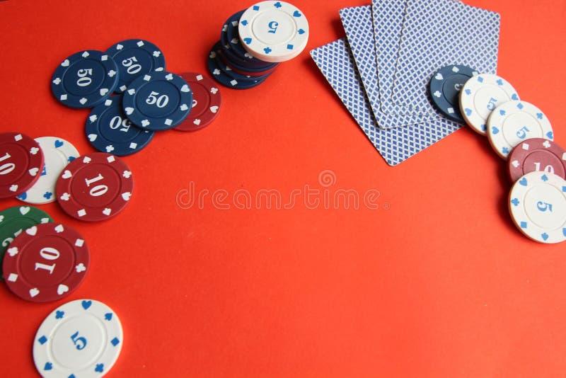 啤牌卡片,pocker芯片,金钱,在红色背景的pocker模子 赌博,棋 免版税库存图片