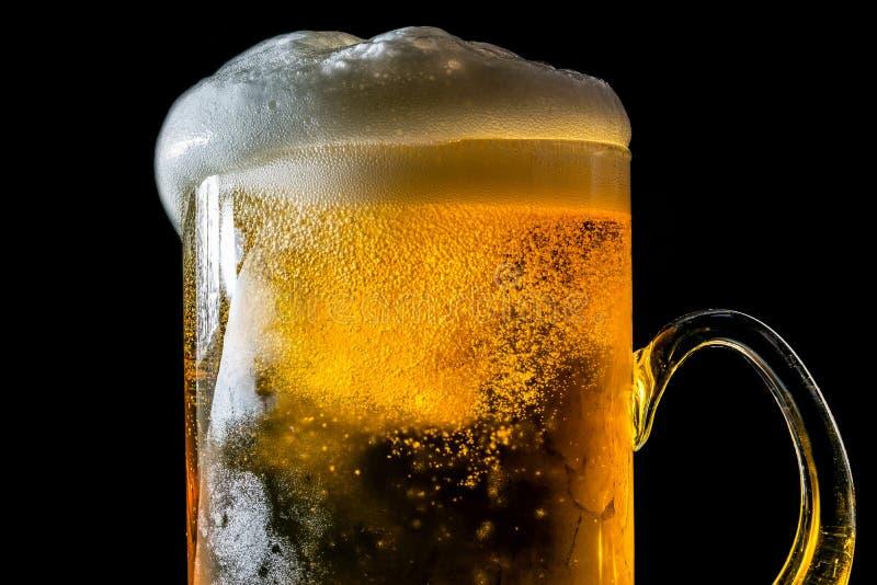 啤酒与泡沫的溢出的大被隔绝的玻璃和泡影 免版税库存照片