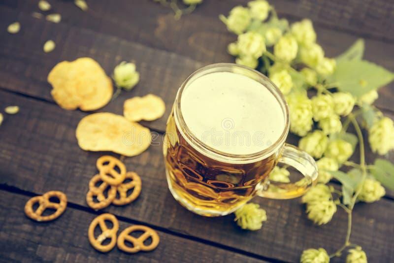 啤酒和快餐在黑木桌上 在玻璃的草稿冰镇啤酒 免版税库存图片