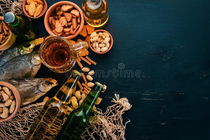 啤酒和快餐的选择 低度黄啤酒,黑啤酒,活啤酒 在黑木背景 r 图库摄影