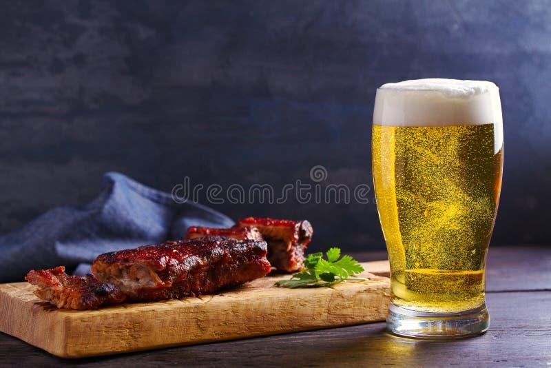 啤酒和猪肉排骨 啤酒和肉 杯强麦酒 图库摄影