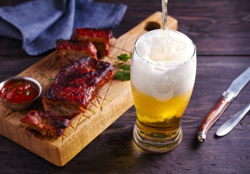 啤酒和猪肉排骨 啤酒和肉 杯强麦酒 免版税库存照片