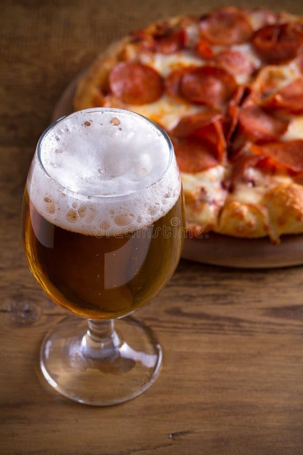 啤酒和辣香肠烘饼在木桌上 杯啤酒 强麦酒和食物概念 库存照片