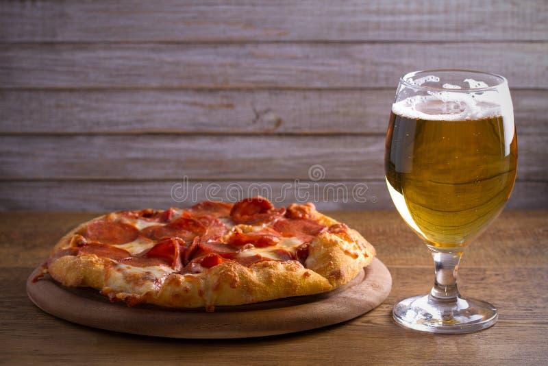 啤酒和辣香肠烘饼在木桌上 杯啤酒 强麦酒和食物概念 免版税库存照片
