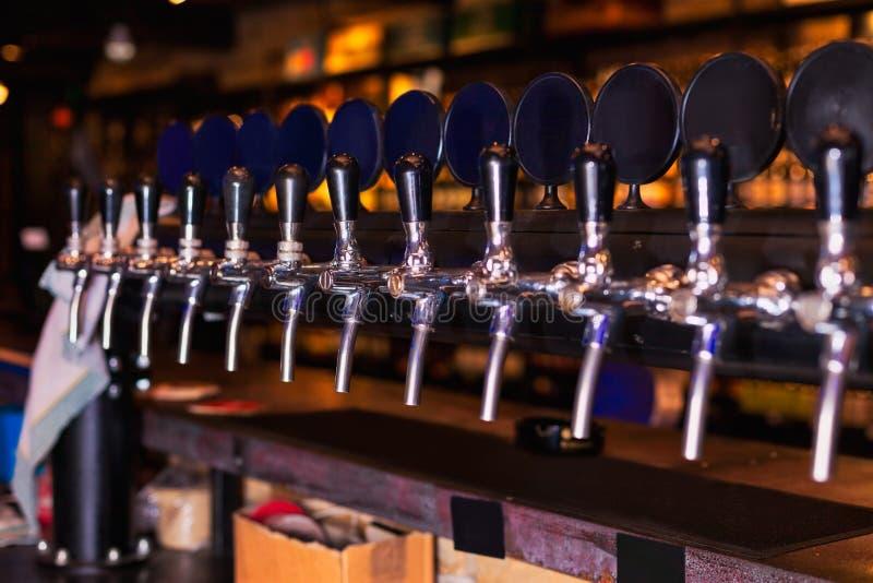 啤酒在酒吧柜台的轻拍行 库存图片